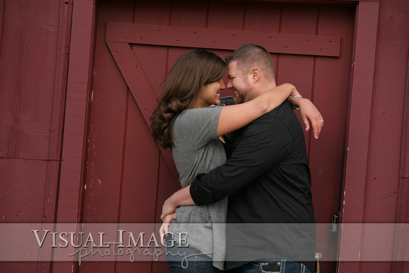 Couple hugging each other and smiling in front of wood barn door