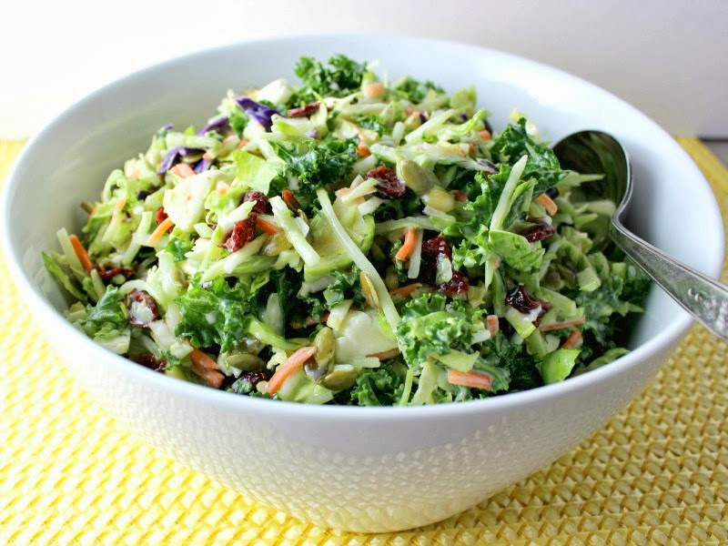 Broccoli, Kale, and Brussels Sprouts Slaw in white bowl, angle view with spoon