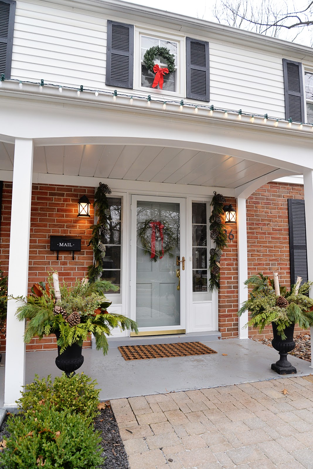 Christmas colonial house with wreaths in windows and DIY outdoor planter