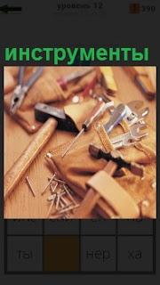 На рабочем столе лежат различные инструменты - молоток, плоскогубцы, струбцина и другие