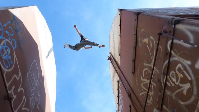 Parkour athlete Stefanno De Lira jumping between train cars
