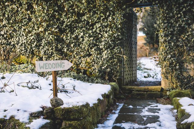 Wooden wedding sign pointing to gap in the hedge