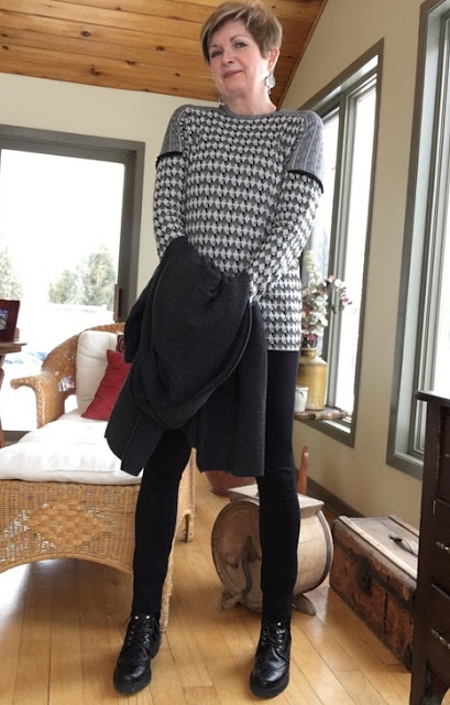 woman in black pants and sweater, checkered tee, holding a charcoal sweater