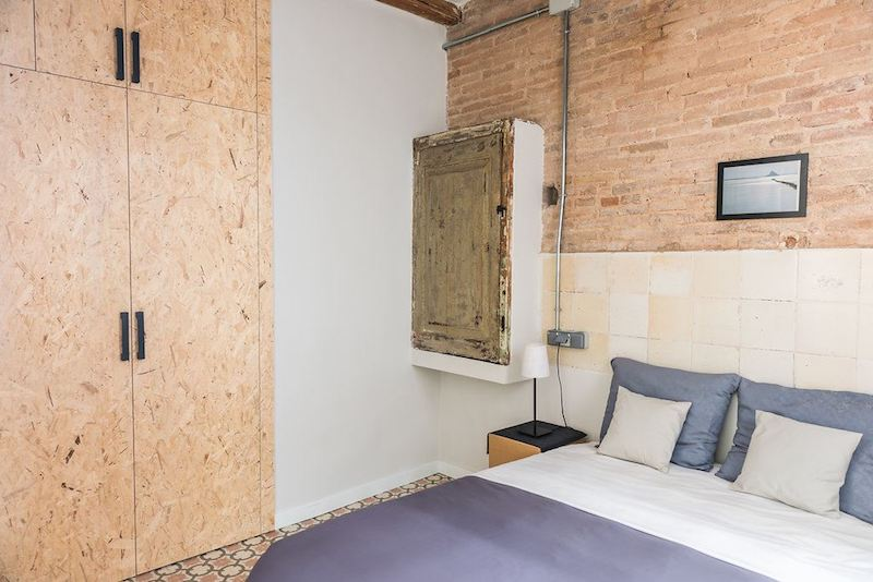 Dormitorio con armario de puertas de madera de OSB y suelo hidráulico