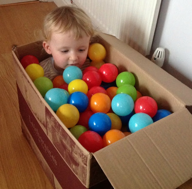 toddler in cardboard box with plastic play balls