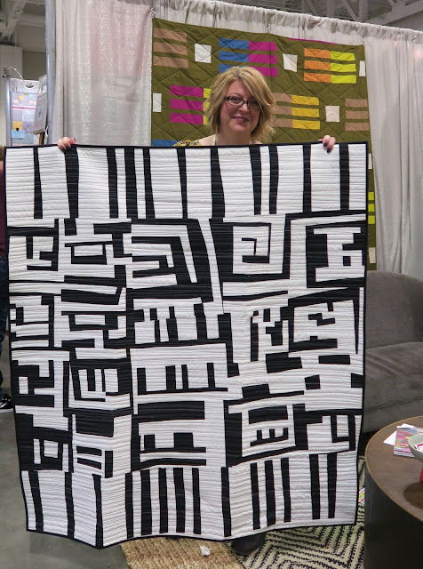 Quiltcon 2019 - Amy and her quilt on Curated Quilts booth