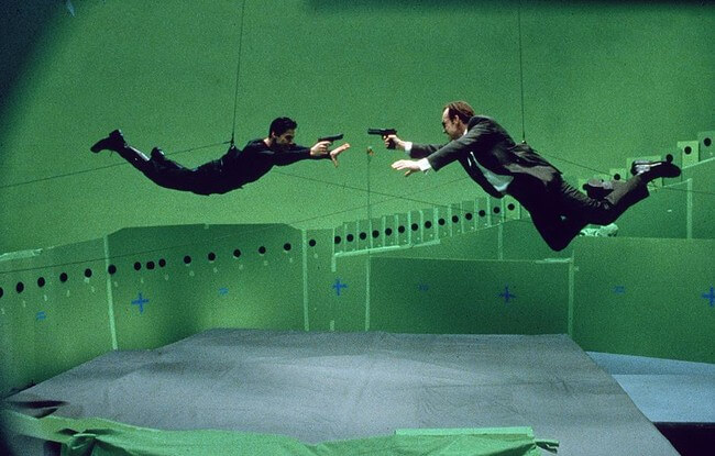 60 Iconic Behind-The-Scenes Pictures Of Actors That Underline The Difference Between Movies And Reality - Keanu Reeves and Hugo Weaving flying away shooting for Matrix.