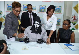 Photo: Jamaican Super Lotto Winner Receives $154million Star Prize under Face Mask.