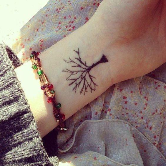 vemos a una mujer joven con un tatuaje pequeño, el tatuaje es de estilo hipster