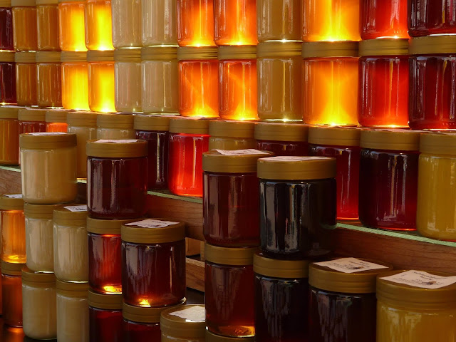 Large number of honey in glass jars placed together