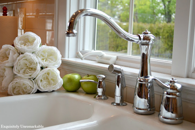Pfister Marielle faucet on white kitchen sink with white roses near it