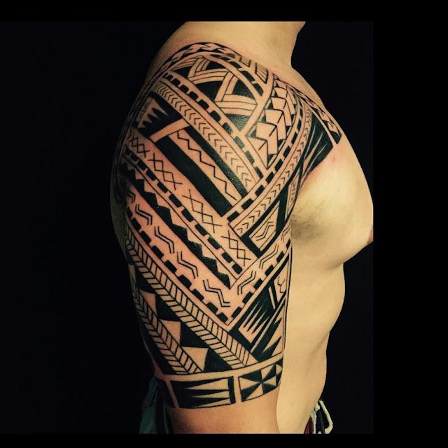 Tatuagem maori encobrindo ombro e braço.
