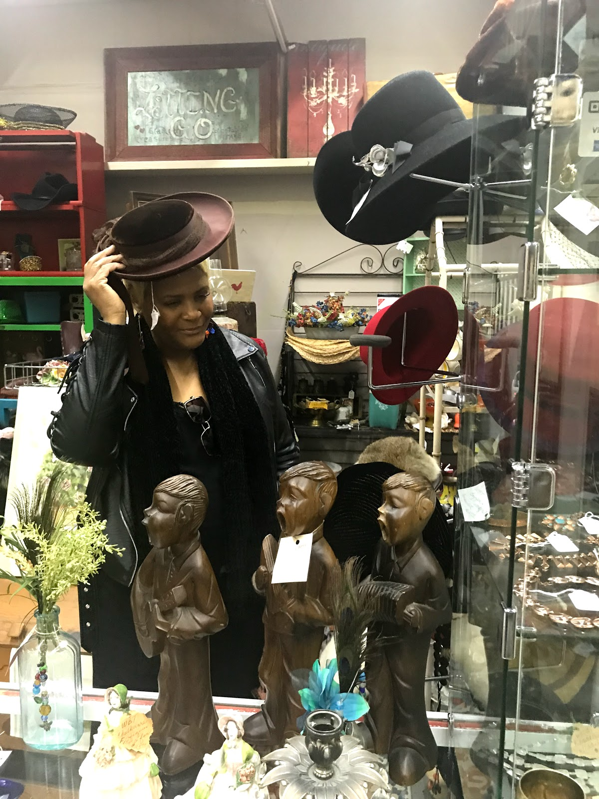 Image: Woman trying on hats at thrift store. Morning Babbes