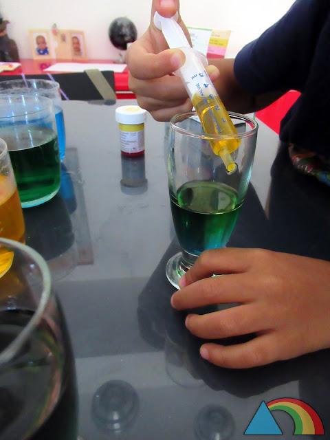 Añadiendo agua coloreada con azúcar a un vaso con la ayuda de una jeringuilla