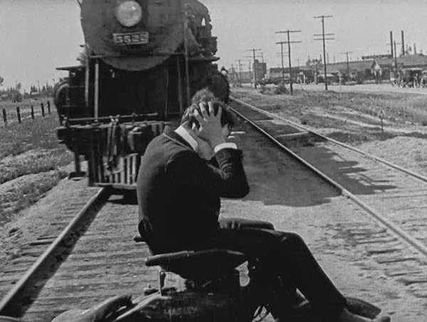 Buster Keaton's projectionist narrowly misses a moving train in his action-movie dream.
