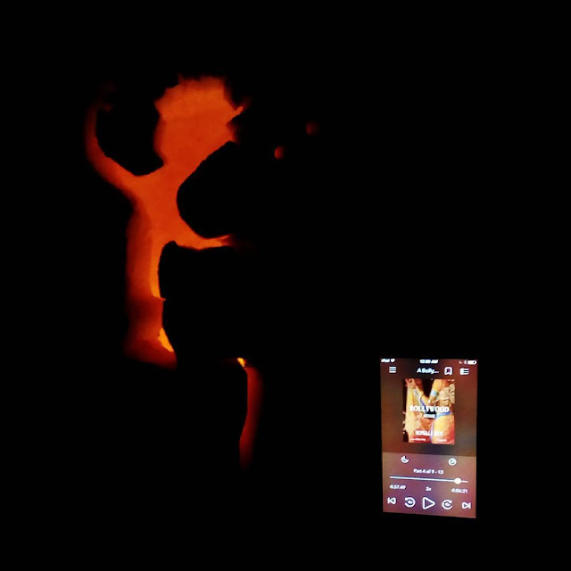 An iPod with the cover of A Bollywood Affair on it appears to the right of a lit pumpkin carved with Dancing Groot from Guardians of the Galaxy. The book's cover features a faceless woman in a pale gold and blue sari.