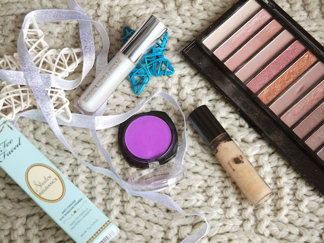 a flatlay with a nude eyeshadow palette, purple eyeshadow, and three tubes of primer on a cream wool background