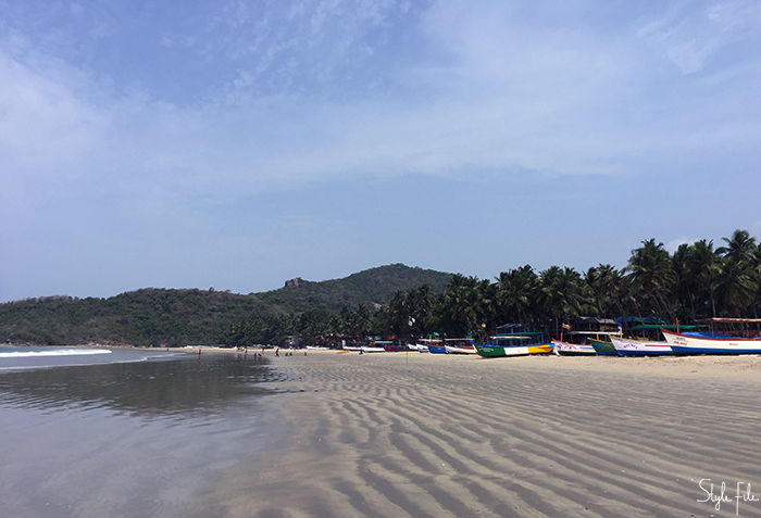 Image of a boats on a beach surrounded by mountains in Goa