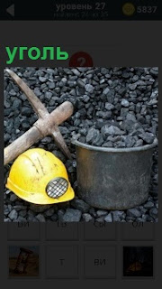 Большая куча угля на которой лежит каска желтого цвета, кирка для добычи и ведро для сбора угля