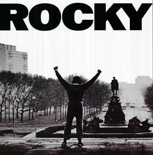 Rocky, 1976. La imagen muestra un fragmento del cartel de la película con Stallone de espaldas con los brazos en alto. Fotografía en blanco y negro