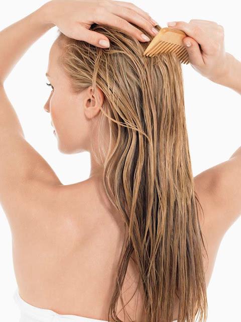 Češljanje duge masne plave kose drvenim češljom