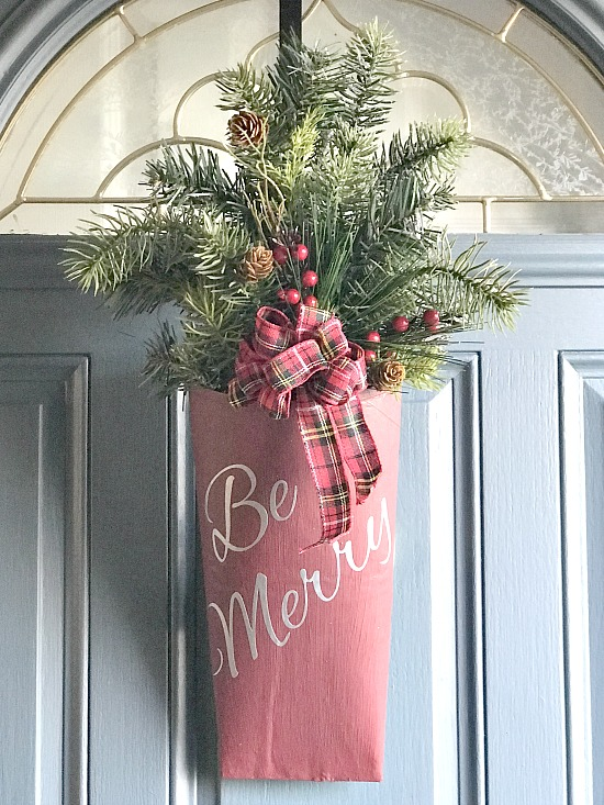 Repurposed door bouquet for the holidays using greens and a vinyl sign