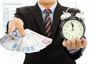 Bir elinde ödeyeceği vergi paraları diğer elinde bir saat tutan mükellef