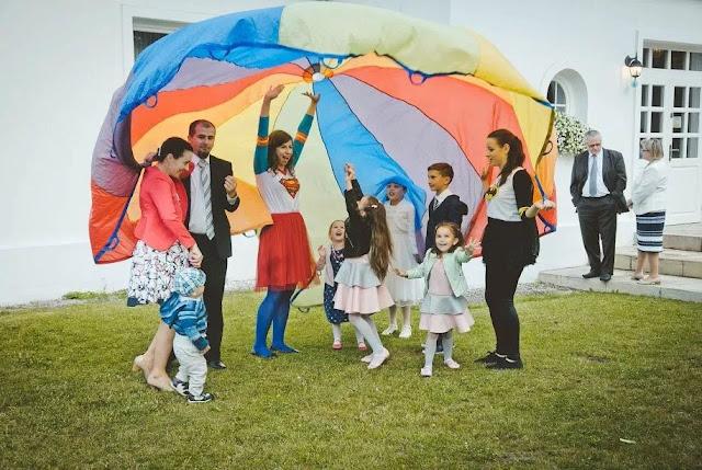 Zabawa z kolorową płachtą dla dzieci na wesele prowadzona przez animatorkę z Wytwórni Przyjęć.