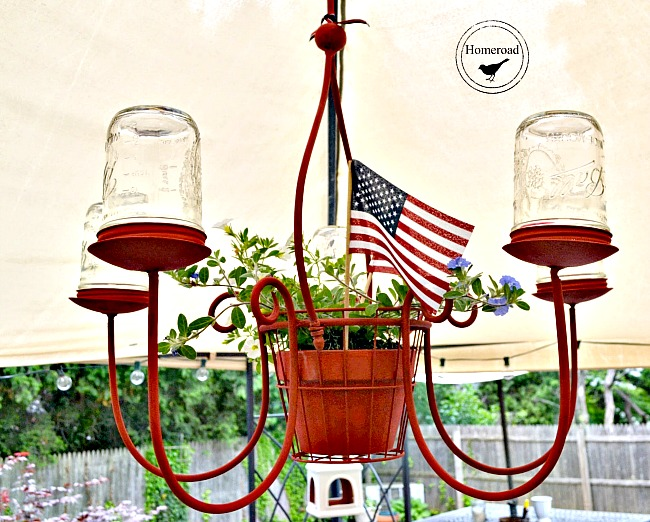 chandelier with red and mason jars and a plant