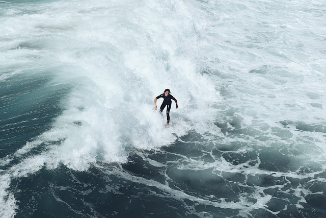 surfer riding a wave in a wetsuit