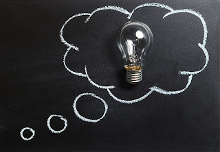 chalkboard with thought bubble drawn in chalk, surrounding an incandescent lightbulb