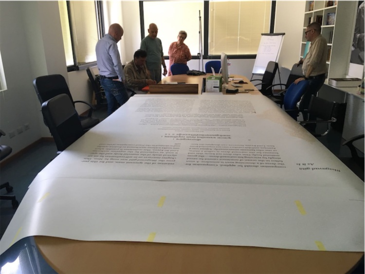 Madhusevita Das and his team are dwarfed as they work on a giant page of the Astounding Bhagavad-gita