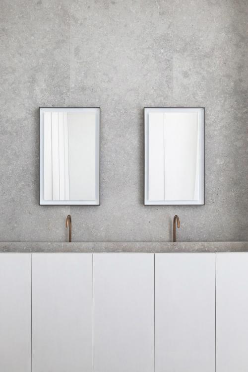 Zwei Spiegel hängen nebeneinander an der Wand aus Steinplatten