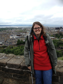 Me in a touristy pose in front of a view of a city in Scotland, holding my white cane.