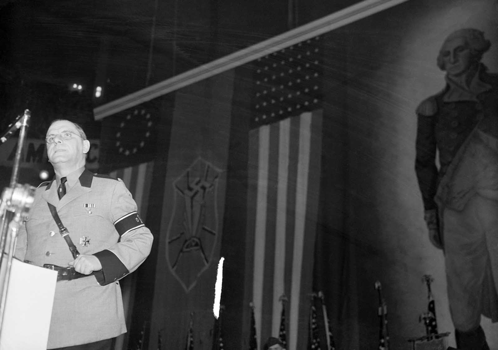 February 20, 1939. Original Caption: The local Fuehrer holds forth. Hewing to the verbal line and letting the syllables fall where they may, Fritz Kuhn, local Fuehrer, leader of the German American Bund, addresses the Bund's heavily guarded