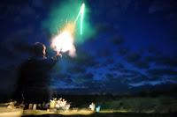 Gece gökyüzüne işaret fişeği tabancasıyla fırlatılan yeşil renkli işaret fişeği