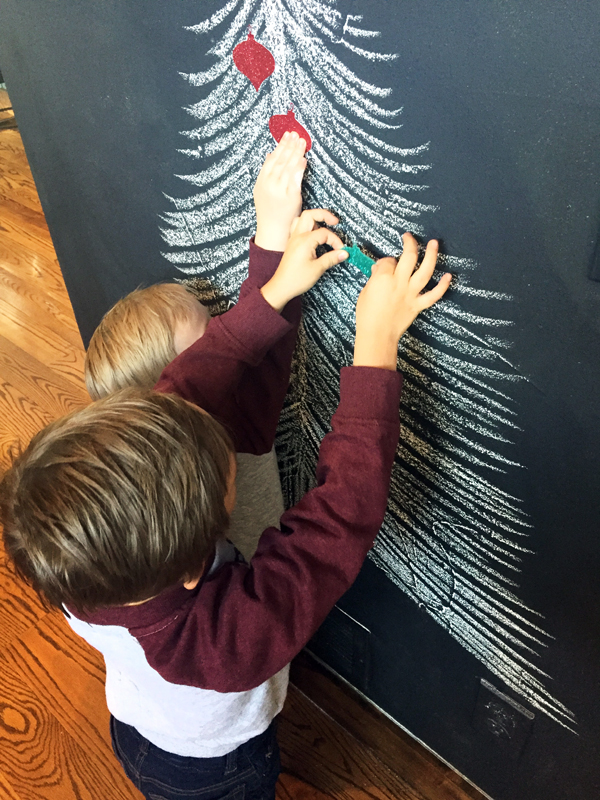 Putting ornament magnets on chalkboard Christmas tree