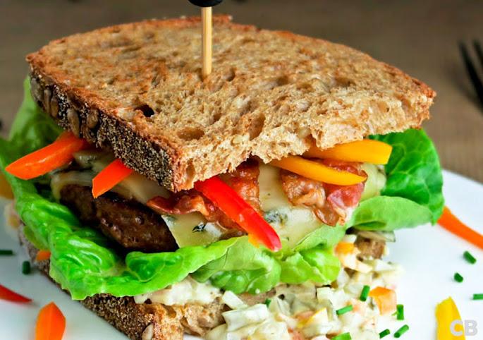 Hamburgersandwich met sweet-bitesaus, rucolakaas en ontbijtspek