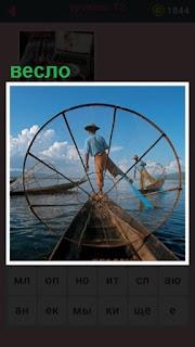 рыбак веслом толкает свою лодку по воде