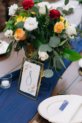 table numbers and yellow red and white flowers centerpieces
