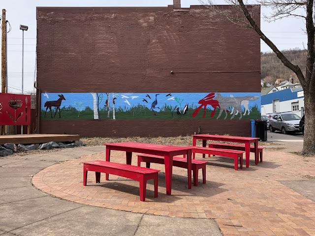 Adorable park set up with tables and a kids' mural in Duluth.