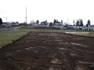 A grass field with a large area of turf removed, exposing bare soil.