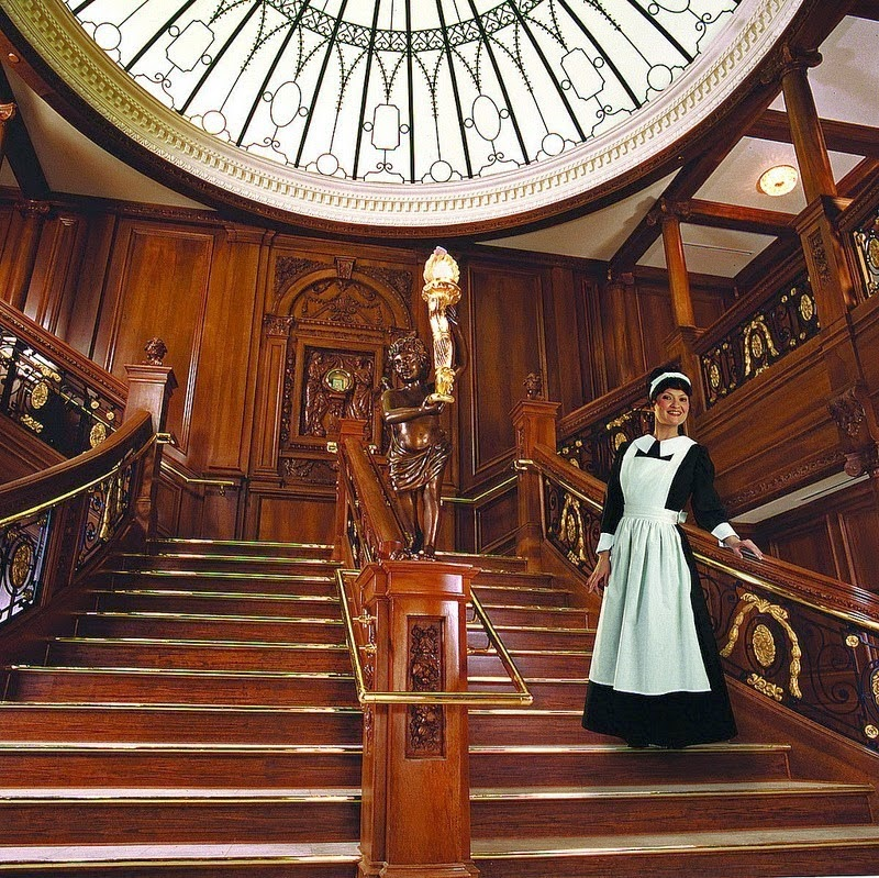 An actor dressed as a chambermaid stands on the Grand Staircase. - The Titanic Museum in Branson