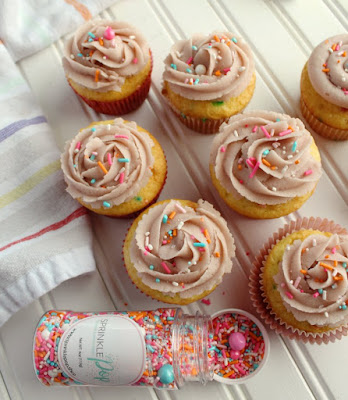 cupcakes with swirls of sugar cookie dough frosting and a bottle of springy sprinkles