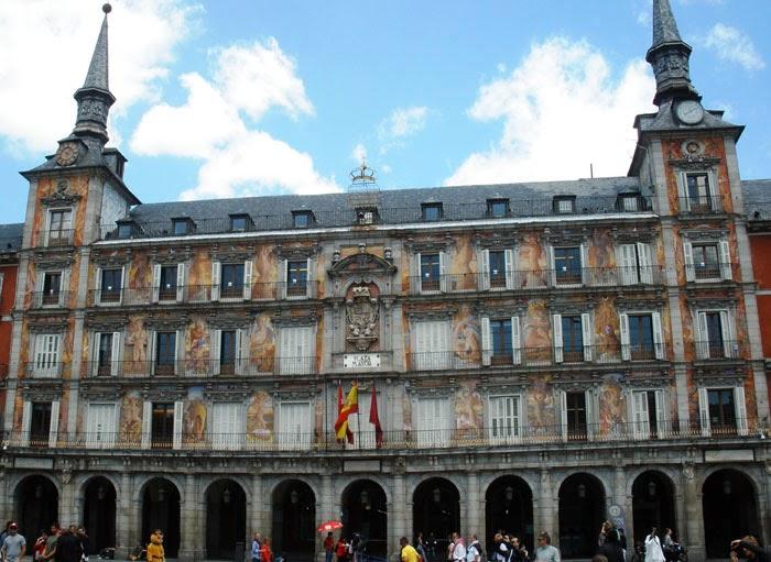 Fachada de la Casa de la Panadería, con sus pinturas, escudo tallado en el centro y torres con reloj en los chapiteles.