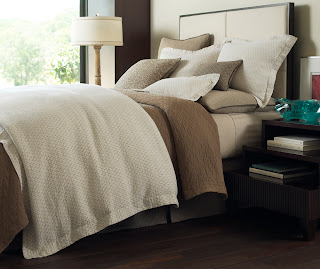 A modern bed styled in shades of white and brown with a wealth of textures for added depth