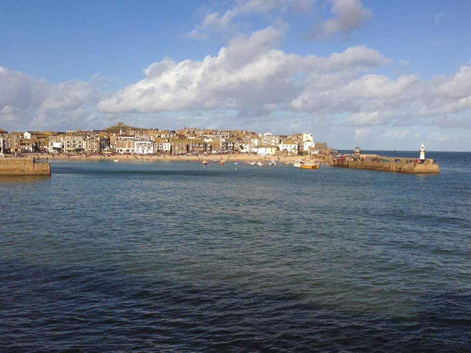 a view of St. Ives from across the bay. Houses and the jetty can be seen