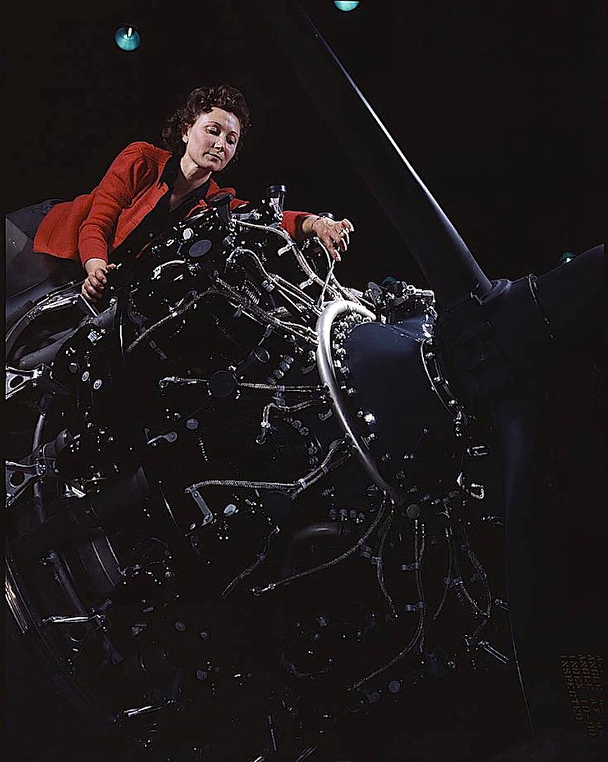 an Alfred T Palmer photograph of a 1942 war worker, a woman adjusting a giant engine