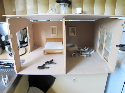 Front view of a dolls; house miniature shed kit, held together with clamps and tape.