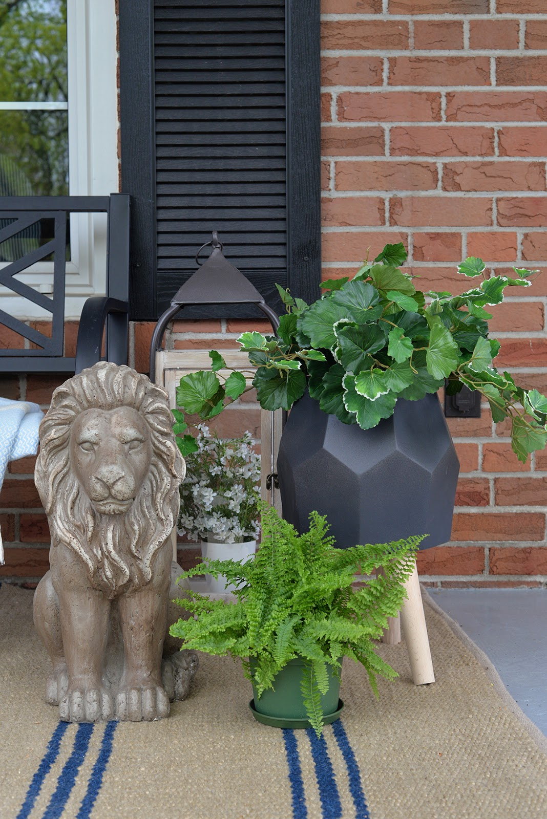 front porch decorated with artificial outdoor plants, outdoor lantern, lion garden statue, geometric planter